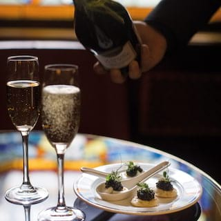 Bubbles rising in two champagne flute glasses on a tray with caviar on blinis