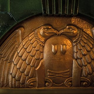 Close-up of a gold-plated relief of two eagles set into an emerald green tiled wall