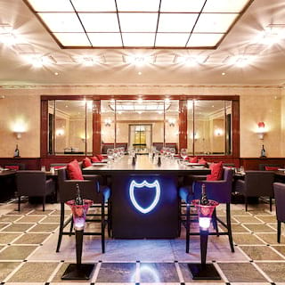 Stylish bar with black leather furnishings and a neon shield on a bar table