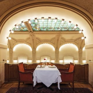 Table for two in an arched alcove of a formal restaurant with a stain glass ceiling