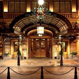 Grand entrance to a hotel with a glass arched canopy over double hardwood doors