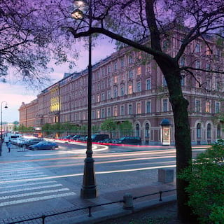 View across a street of a grand art-nouveau hotel under a purple sunset