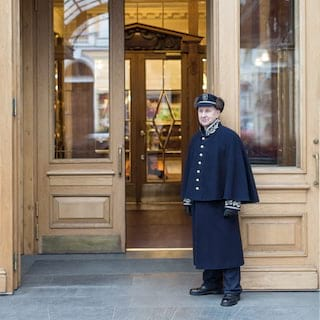 Smiling doorman in a navy and gold embroidered cape and hat at a hotel entrance