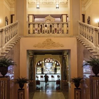 Two grand staircases leading from a double-height lobby with a marble floor