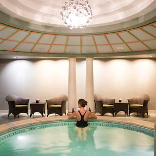 Lady standing at the far edge of a circular plunge pool under a domed roof