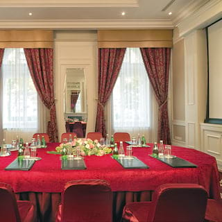 Oval boardroom table with a bright red tablecloth set with pens and pads for a meeting