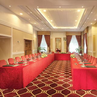 Banquet tables in a 'U' formation with bright red tablecloths set for a meeting