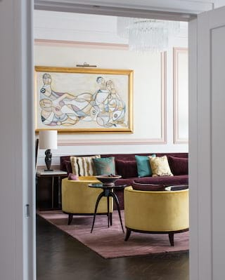 Stylish hotel room lounge area with canary yellow armchairs and plum velvet sofa