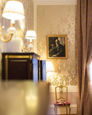 A gold baroque-style chair against a dusk pink and cream patterned wall