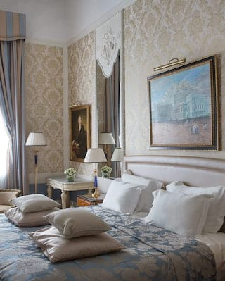 Double-height hotel room with light-blue silk patterned bedspread and pale cream walls