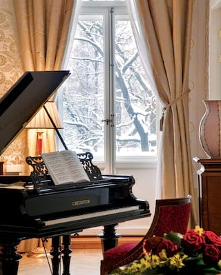 Close-up of a baby grand piano with views through a window of a snowy landscape