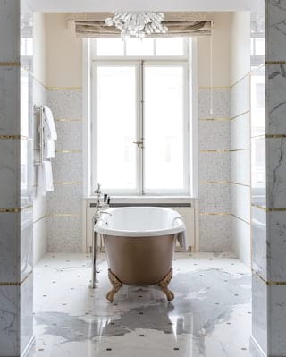 Standalone bathtub with claw feet in a marble tiled bathroom with gold details