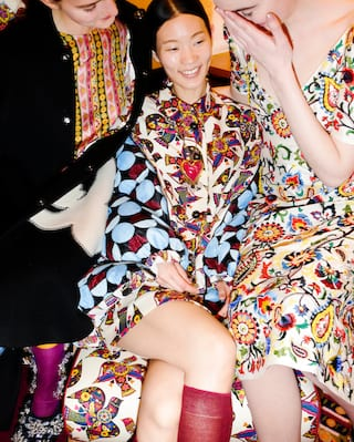 Ladies in a multi-patterned dresses smiling