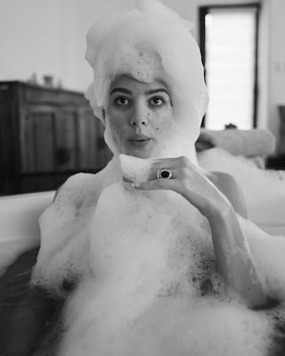 Lady in a bubble bath blowing bubbles from her hand