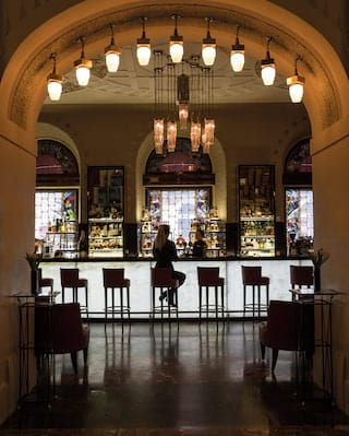 Silhouette of a lady on bar stool at a bright backlit bar in front of arched windows