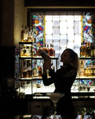 Silhouette of a barwoman with a cocktail shaker at a bar with stained glass windows