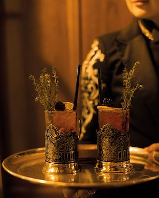 Two cocktails with thyme sprigs in glasses with engraved silver surrounds