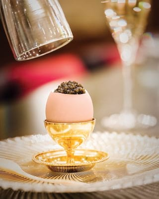 Close-up of a pink egg shell topped with caviar in a bright gold egg cup