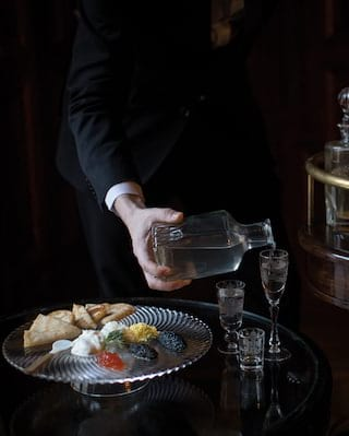 Hand pouring vodka from a glass carafe into glasses beside a silver tray of caviar
