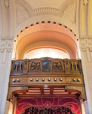Close-up of a balcony wall made of intricately carved mahogany under an archway
