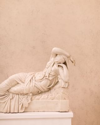 Close-up of a marble statuette of a Grecian woman lounging in a robe dress