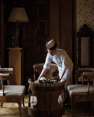 Chocolatier in chef whites placing a tray of white chocolates at a coffee table