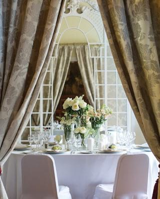 View through double doors of a circular banquet table with a white rose centrepiece