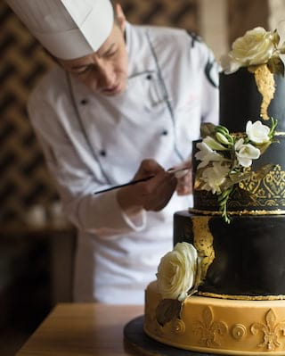 Close-up of a black tiered wedding cake with gold details, topped with white roses