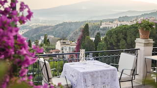 Table for two on an outdoor villa terrace with views across Taormina