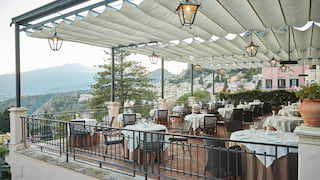 Open-air restaurant terrace with hanging lanterns on a canvas awning