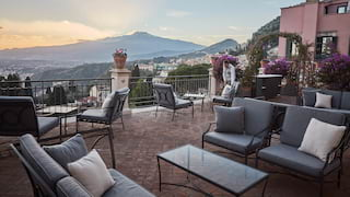Raised terrace with comfy seating and views of Mount Etna across Taormina