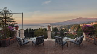 Villa terrace seating area with uninterrupted views of Mount Etna at sunset