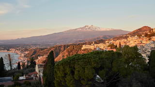 View across Taormina of snow-capped Mount Etna rising in the distance