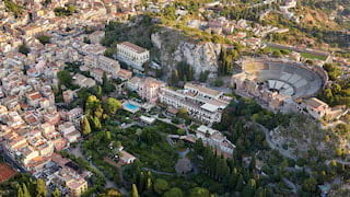 Aerial shot of Taormina with views of an ancient Greek theatre and grand residences