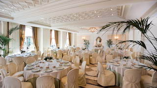Vast ballroom set for a wedding with ornate white corniced ceiling