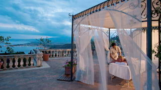 Massage table under an ornate wrought-iron pergola on an Italian villa terrace