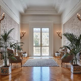Spacious double-height hall with potted palm plants and a parquet floor