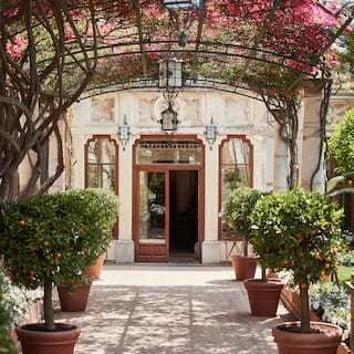 Stone-carved hotel entrance beyond an orange tree lined path under arched vines