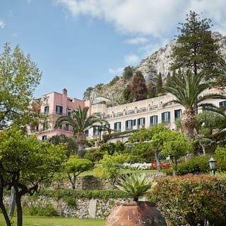 Lush, tiered gardens spilling down a hillside from a grand hotel