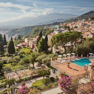 Aerial view of a hilltop villa with an outdoor pool and Mount Etna in the distance