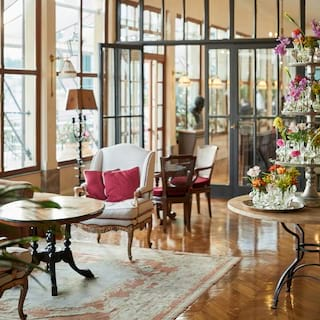 Hotel lobby with a gleaming parquet floor, plush armchairs and tiered floral stand
