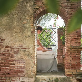 View through an arch in a brick wall of a spa therapist massaging a lady