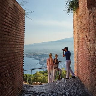 Three guests in a cobbled alley taking photographs of Taormina bay beyond