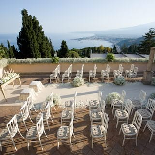 Rows of white wedding chairs on an outdoor terrace with views of Mount Etna
