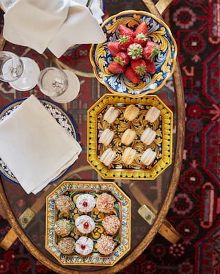 Birds-eye-view of strawberries in a bowl and macarons on a platter