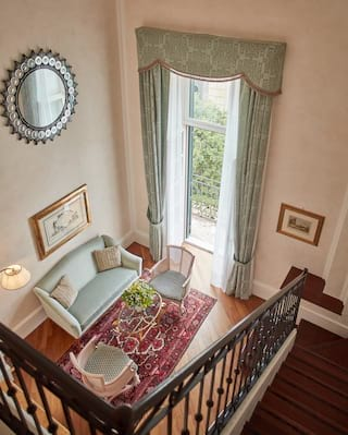 Birds-eye-view of stairs leading into a lounge area with light teal furnishings