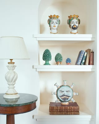 Close-up ceramic ornaments on two shelves inset into a wall alcove
