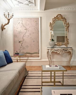 Lounge area with a baroque style mirror next to a floral wallpaper panel feature