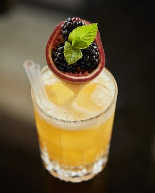 Passion fruit cocktail garnished with blackberries in a pomegranate shell