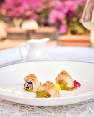 Close-up of a langoustine dish garnished with edible flowers on a white plate